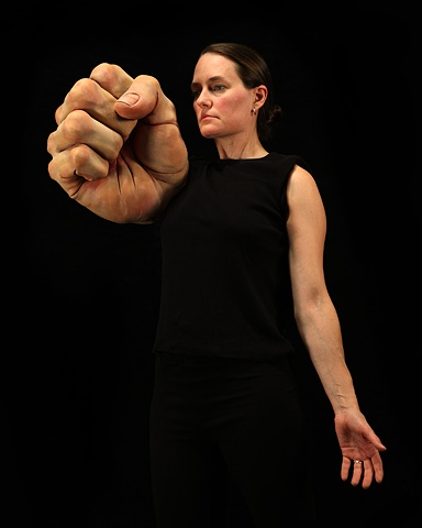 Digital C-Print of  a woman with with a very large sculpted fist on a black background