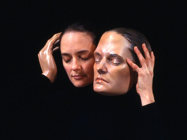 Cibachrome of woman holding a sculpted head next to her own with a mannequin hand