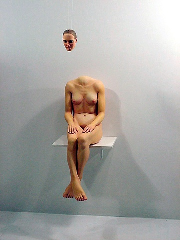 figurative polychrome sculpture which uses perspective to put a head on a headless bosy, smaller than life-size seated on a shelf