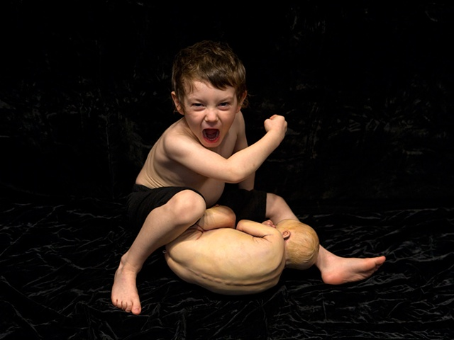 Digital C-Print of a boy in an aggressive pose over a sculpted baby