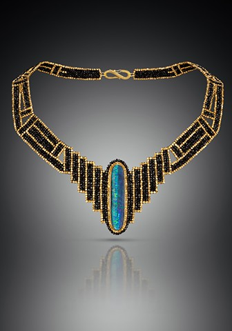 This dramatic collar features a boulder opal in an 18k gold handmade setting.  It is surrounded by a neckpiece that is hand-woven of black spinel and 18k gold beads.