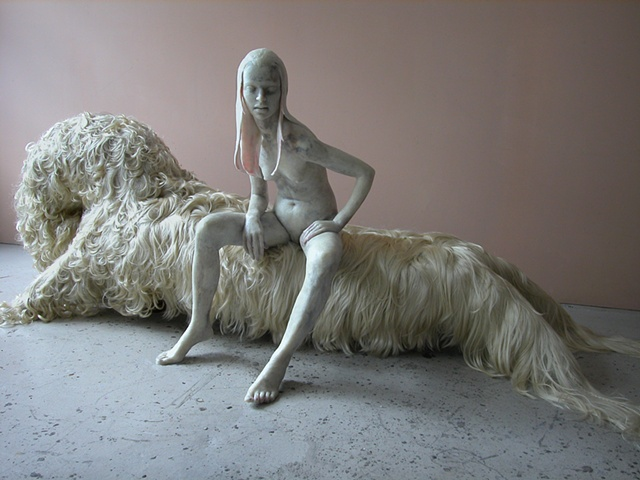 Figure modeled in microcrystalline wax sitting on a chaise upholstered in synthetic human hair
