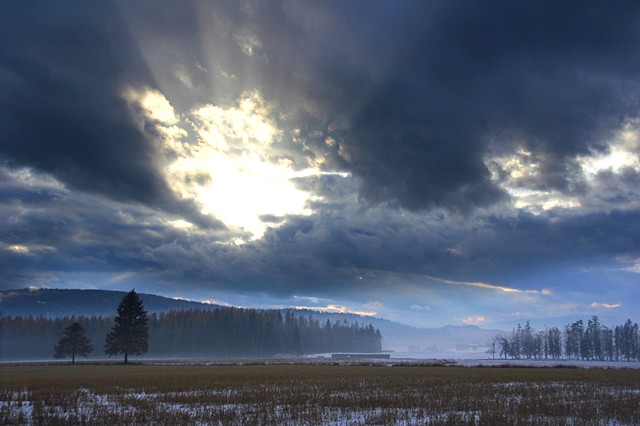 Mist and clouds mute a November sunset in the Flathead Valley, Montana.