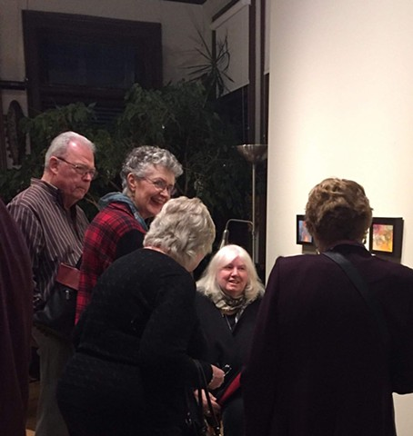 Patricia Moore talking to attendees on  opening night at Gallery on the Bay