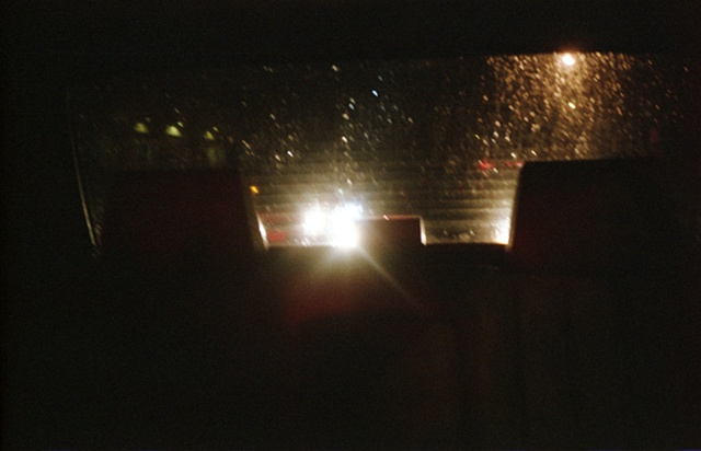 color photograph out back window of car at night by iris grimm