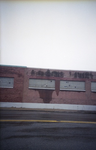 color photograph of brick building and street in rain by iris grimm