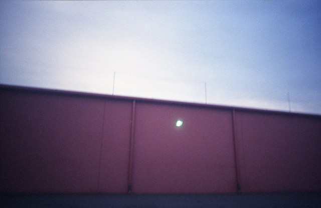 color photograph of a light on a red building by iris grimm