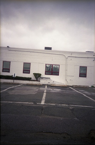 color photograph of an office building and parking lot by iris grimm