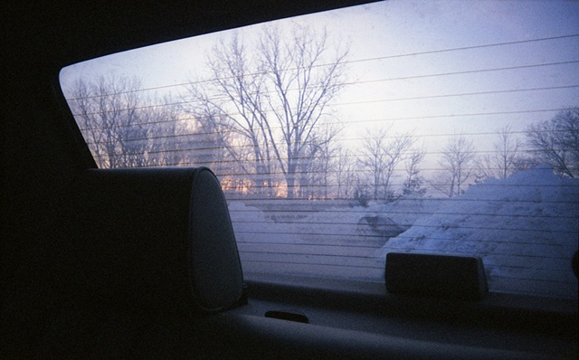 color photograph of sunset and snow through the back window of a car by iris grimm