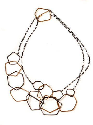necklace of oxidized silver & brass hexagons & pentagons; adjustable, can be doubled.