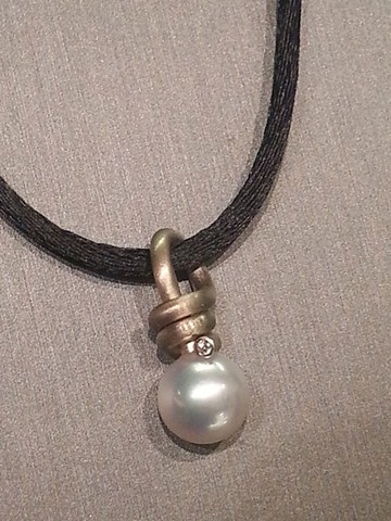 A pearl pendant in 14 karat palladium white gold with diamond accent