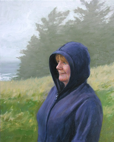 Woman in blue hooded sweatshirt, ocean and firs in foggy background.