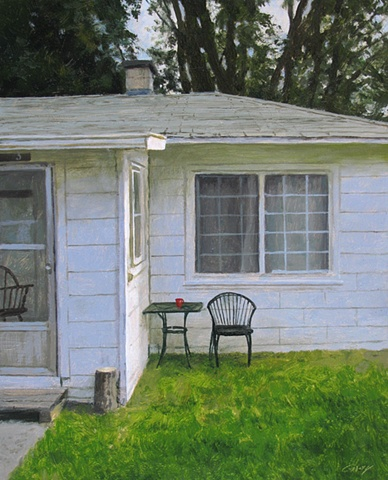 White cottage, green grass, lawn chair.