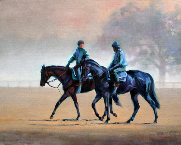 Two early morning riders near a racetrack.