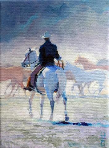 A cowboy on a grey horse herding horses into a corral.