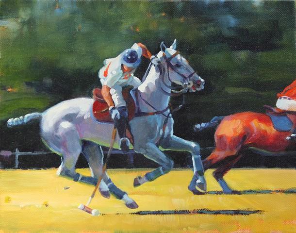Polo player riding grey polo pony in polo match.