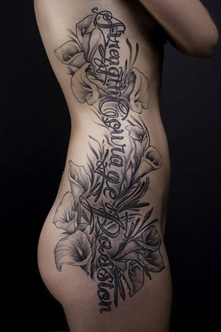 Script lily flower rib tattoo