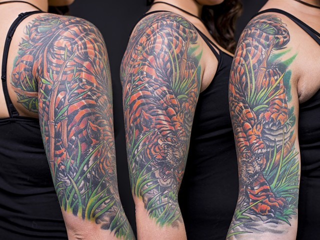 Tiger in the grass bamboo half sleeve colour tattoo