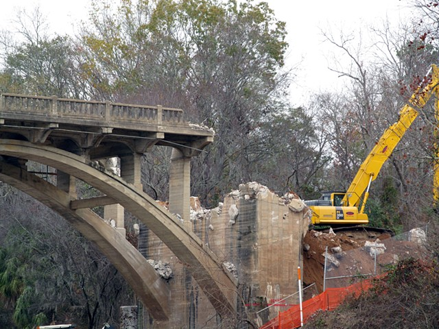 Down river from the bridge.  A crane clears rubble from demolished end on the East side of the Flint.