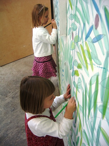 """little girls drawing on the wall of an olive grove sanctuary theatrical installation environment by Eugenia Mitsanas for """"Olive Grove Project"""" at Workspace Ltd."""