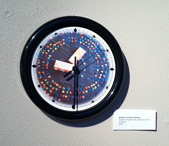 Black rimmed clock with LifeCycle image as the face.