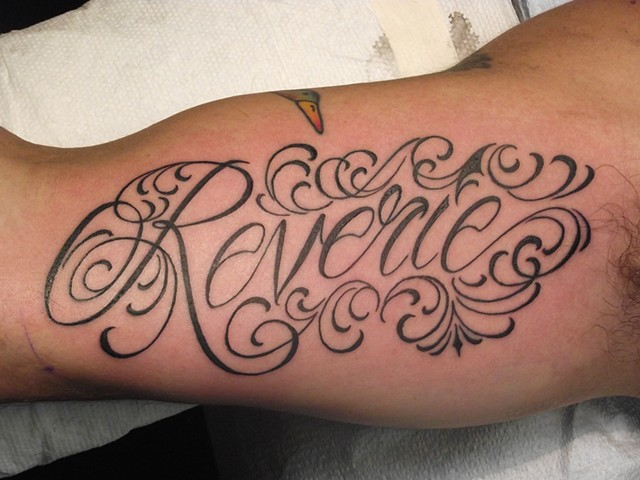 Black & gray text. Arm tattoo.