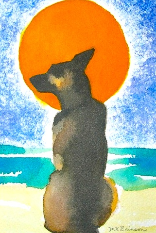 A German Shepherd dog sits on the beach before a big orange sun.