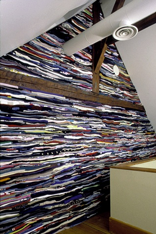 Art installation of wall of folded used clothes in textile museum