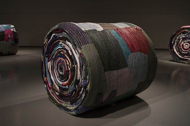 Art installation of full scale round bales made out of used clothing and bale netting