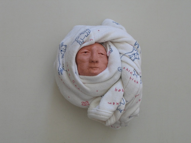 Individually modeled, walnut-sized clay heads, wrapped in baby sleepers and arranged on gallery floor with rain forest photomural