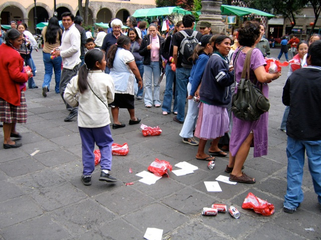 cans of coke are dumped for this art performance with viewer participation in a Mexico City market square