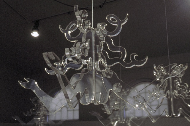 Art installation of eight figurative revolving clear plexiglas chandeliers