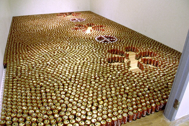 "empty coke cans arranged on the floor in a ""peace and love"" pattern"