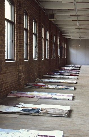 Art installation of bed-forms made of folded used clothes