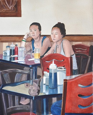 Two young women sit down in a coffee shop, one sad, one seemingly happy