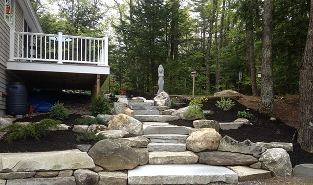 Granite steps and walkways with granite and boulder retaining walls.