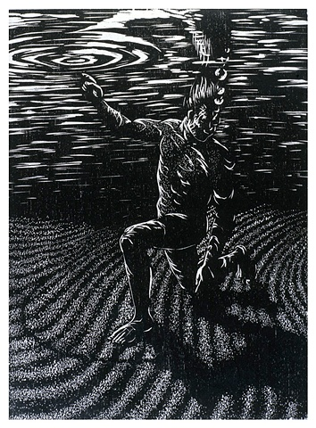 man under water draws on sand with left hand and points to water surface with right hand