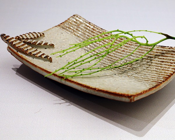 Textured stoneware sushi-plate with applied decoration and glazed with shino and iron oxide