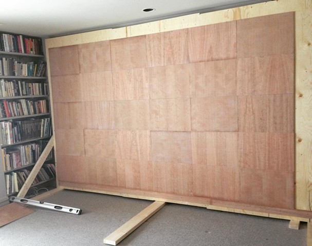 Plywood wall with 30 sanded and varnished cherry panels mounted and ready for drawing