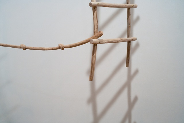 Wood sculpture of ladder and carved knotted rope by Lin Lisberger