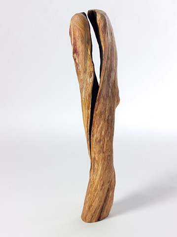 Carved wood sculpture about spaces between by Lin Lisberger