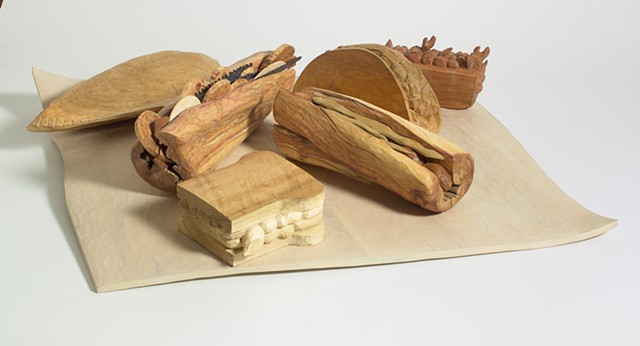 Carved wood sandwiches on a wood cloth by Lin Lisberger