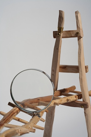Wood sculpture of bridge with magnifying glass by Lin Lisberger