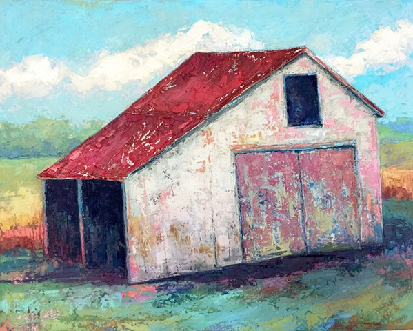 White barn with red roof with farm landscape