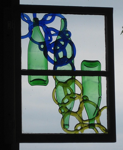 A gate.  Bottle glass in old sash.