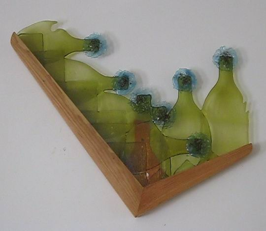 Bottle glass, fused swarf, red frit, wood.  A wall piece.
