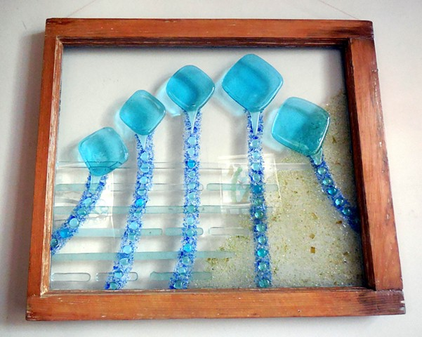 Bottle glass, aquarium buttons, blue and yellow unfired swarf, plate glass in an old window.