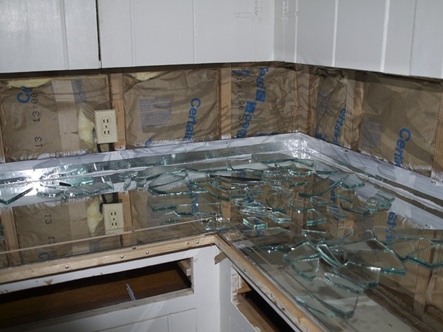 Back splash is removed and insulation was added. Wood is sealed and taped up the wall and Sherry's closet door mirrors are laid in the mold first and then broken mirror is laid on that. This will give the appearance of light coming up through the counter