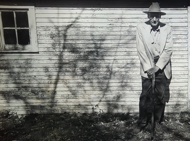 William Burroughs standing next to his garage in Lawrence, Kansas