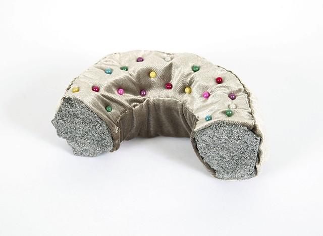 small sculpture of half donut with silver velvet fabric and multicolored pin heads